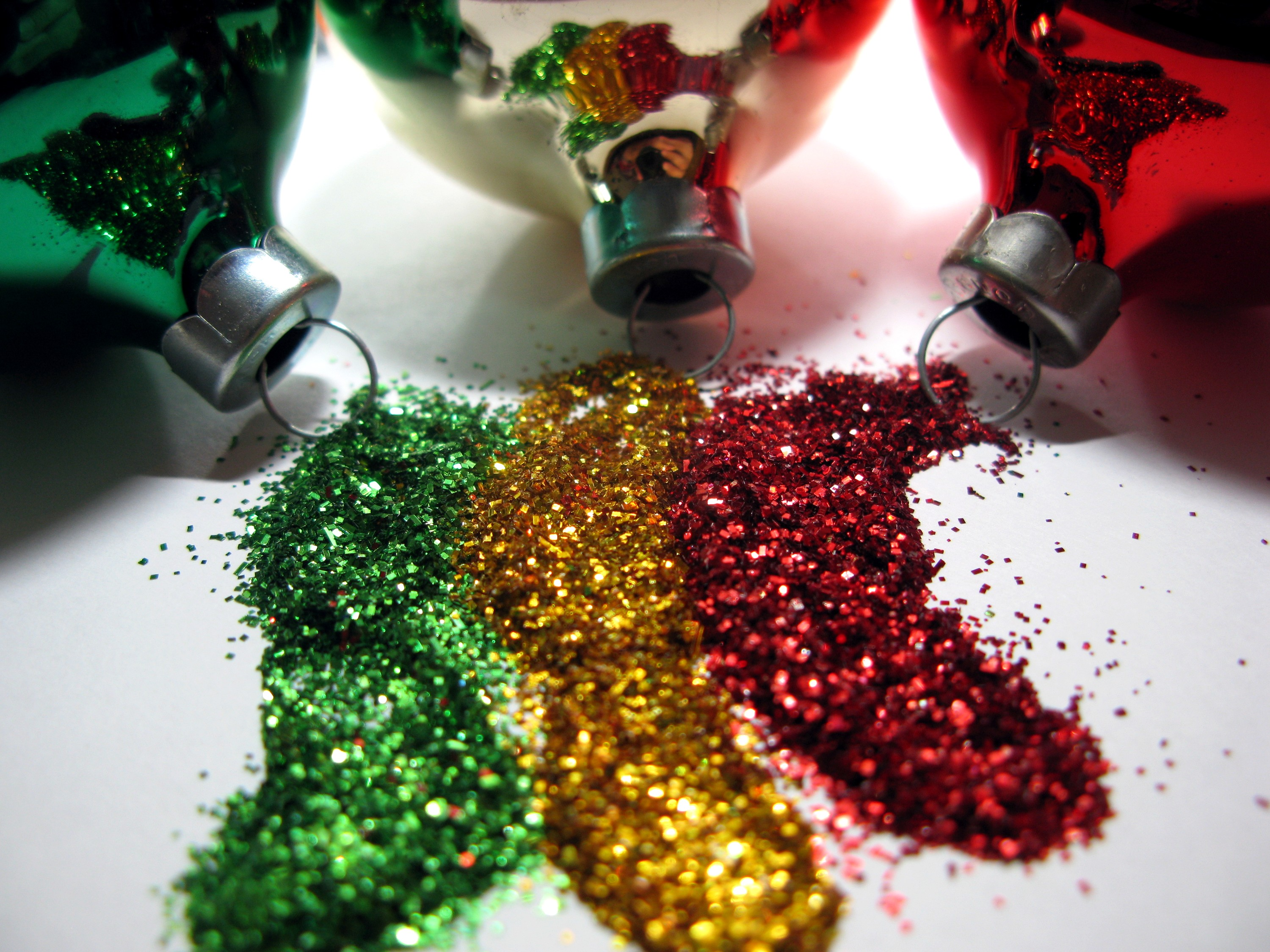 Three Christmas ornaments spilling glitter in green, gold, and red.