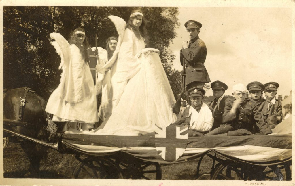 postcard-image-of-wwI-era-parade-float-with-women-dressed-as-angels-and-boys-in-military-uniform