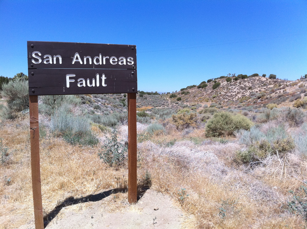 "Image of hills and scrub, with wooden sign that says ""San Andreas Fault"" used under CC BY-SA 2.0 license under Creative Commons"