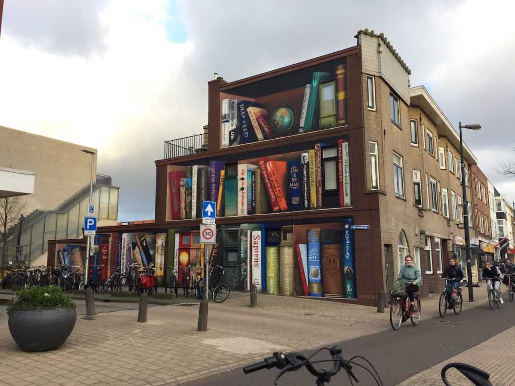 Image of Utrecht, Netherlands apartment building with one side painted to resemble a bookshelf stocked with local residents' recommended titles (street artist Jan Is De Man and tattoo artist Deef Feed)