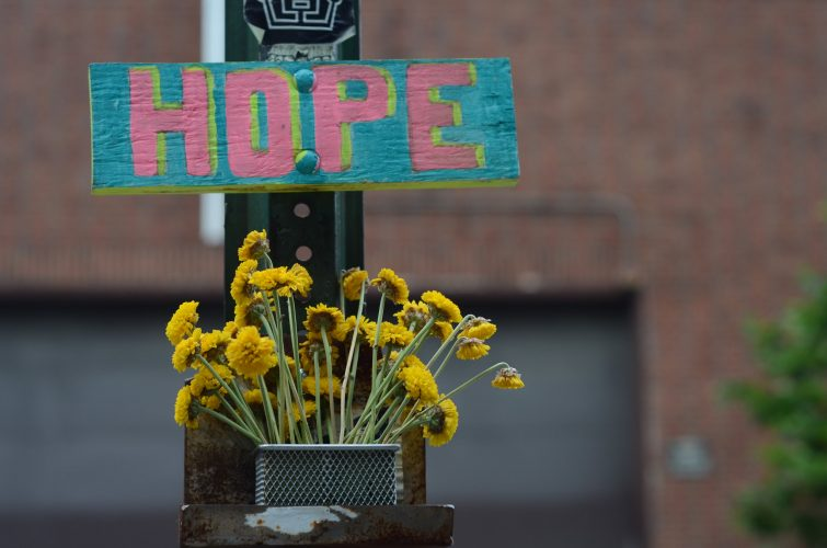 "Wooden sign with ""Hope"" painted on it over a bouquet of yellow daisies. Hope by Gedalya AKA David Gott, used under CC 2.0 license https://creativecommons.org/licenses/by/2.0/legalcode"