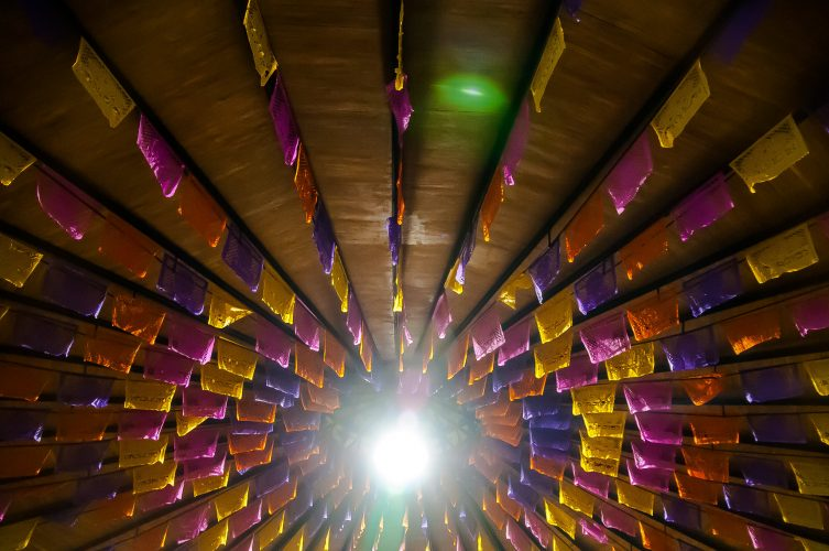 "Image of ceiling with pink, yelllow and purple papel picado hung in rays from central bright light-""Danza de Papel Picado by Eneas De Troya used under cc by 2.0 license without edit or adaptation"