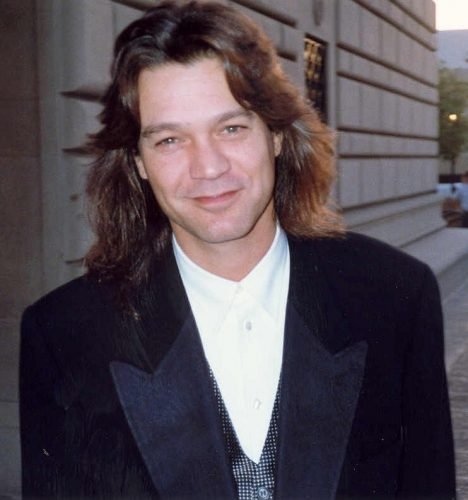 Color image of Eddie Van Halen in shirt and jacket, with long hair. Image dates from 1993 by Alan Light, used under CC by 2.0 license from wikimedia.