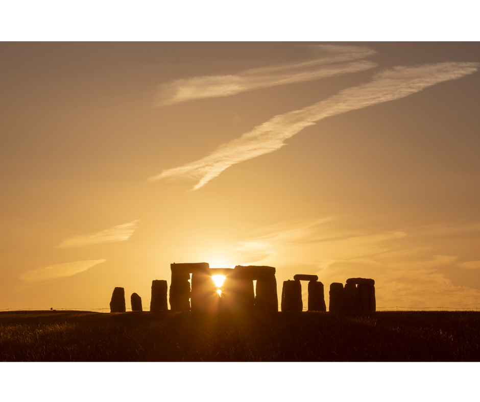 photograph of Stonehenge (in silhouette) with setting (or rising) sun shining through the monument stones