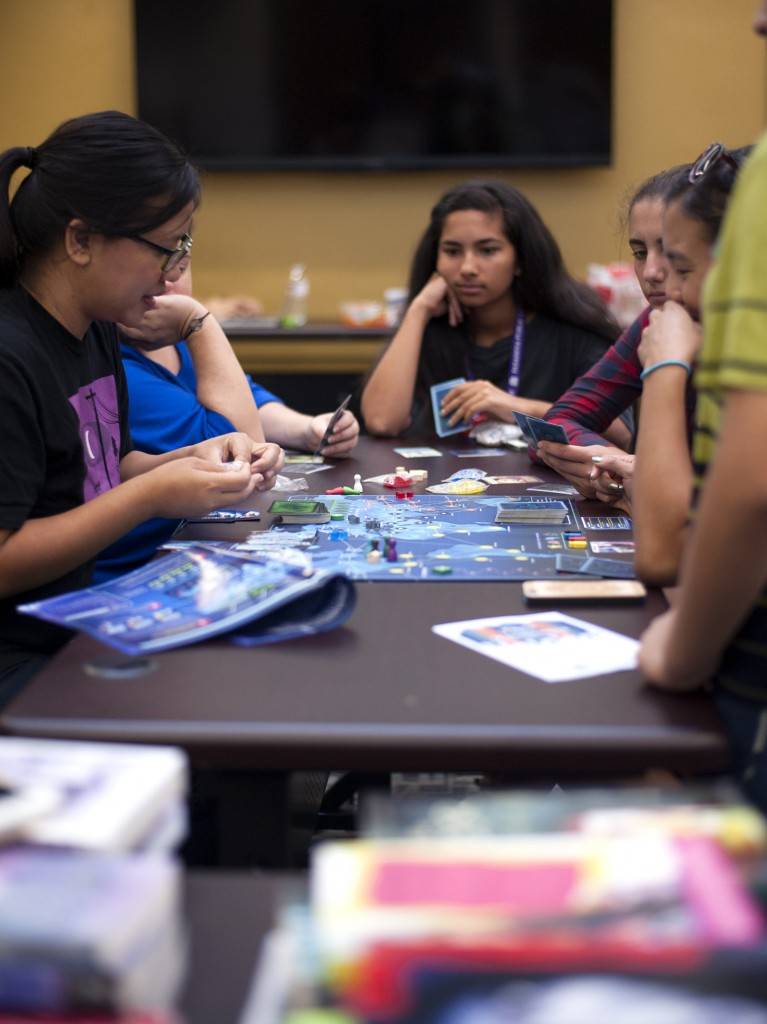 Teens learning to play Pandemic Photo by Katie Ferguson