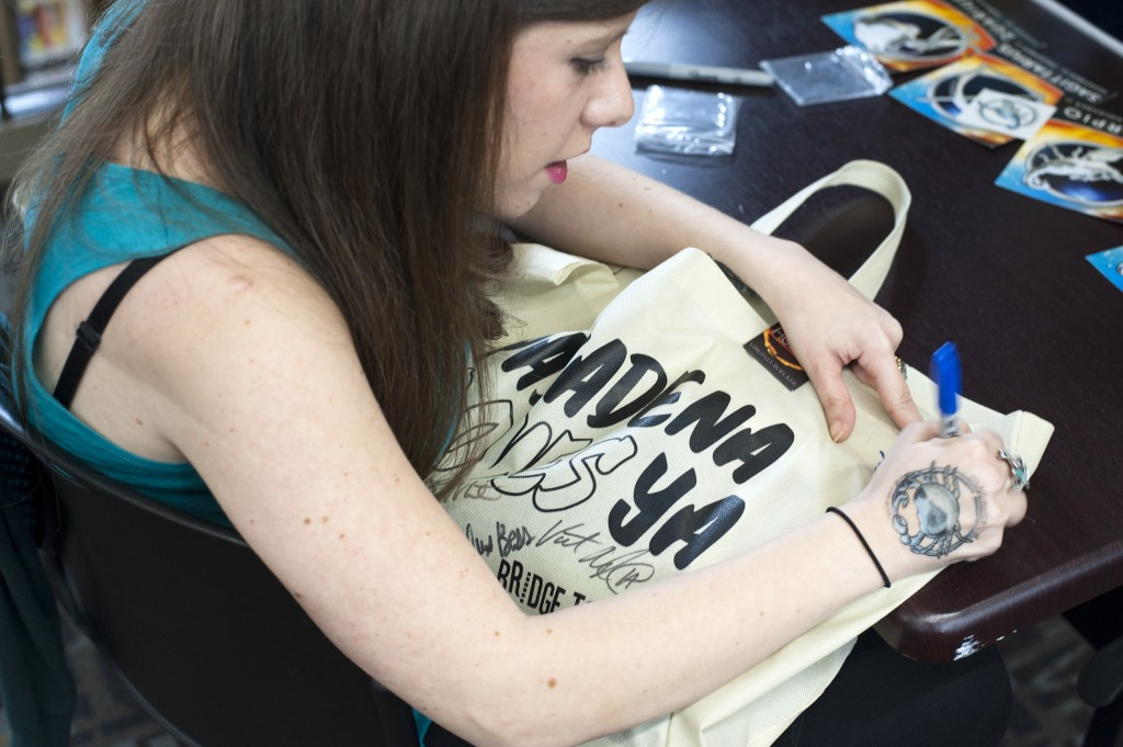 Romina Russell, author of Zodiac signing a Pasadena Loves YA tote for a fan. Photo by Katie Ferguson