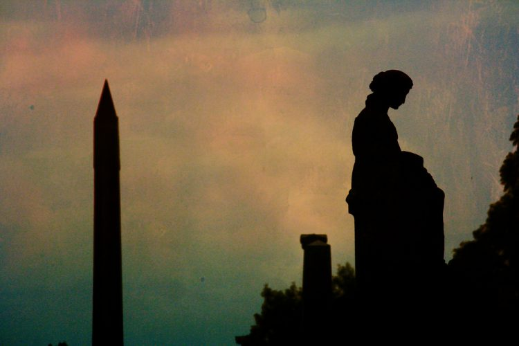 Silhouettes of cemetary statue and obelisk