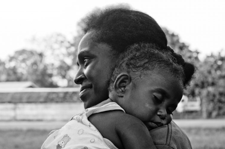 Mother holding sleeping child.
