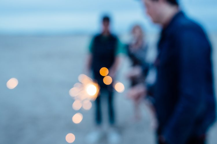Blurry picture of people with sparklers.