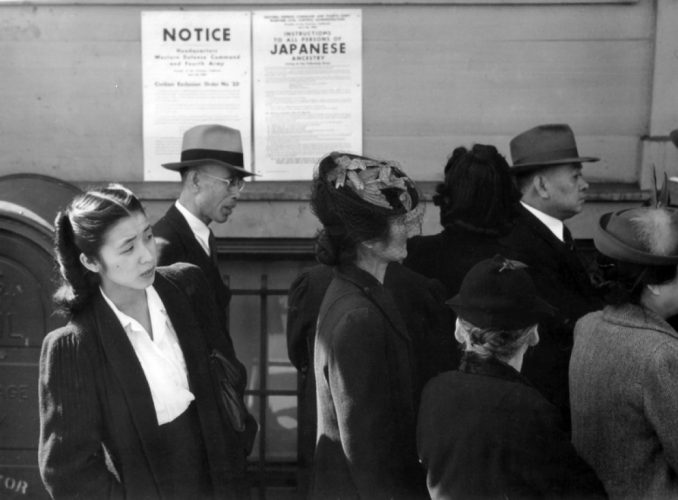 Japanese Americans standing in front of an internment order.