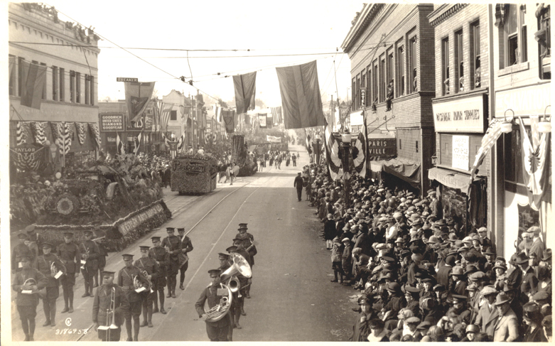 Image of Rose Parade band in street with people lined up on both sides, 1926